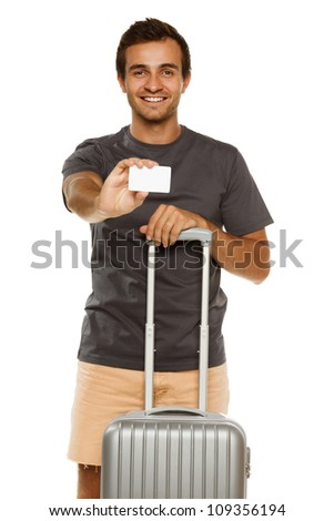 Young smiling male with suitcase showing empty credit card. Focus on man. - stock photo