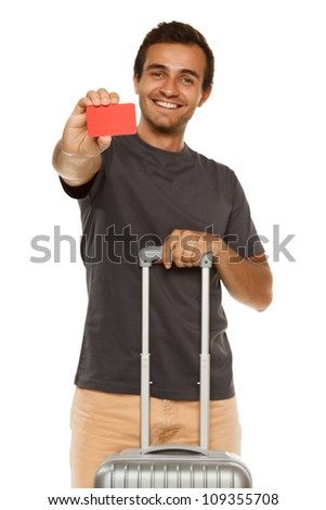 Young smiling male with suitcase showing empty credit card. Shallow depth of field, focus on credit card. - stock photo