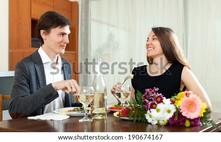 Young smiling man and woman having romantic dinner in home