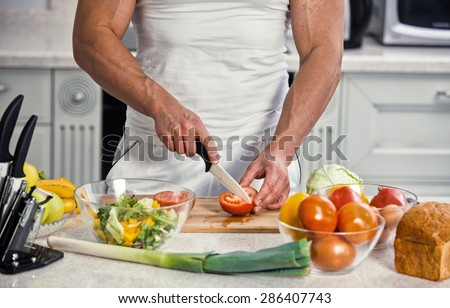 Young smiling man cooking in the kitchen