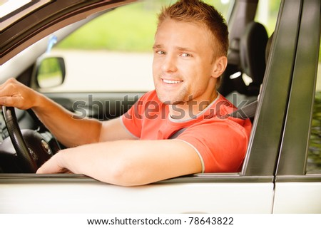 Young smiling man-driver in red clothes at wheel car.