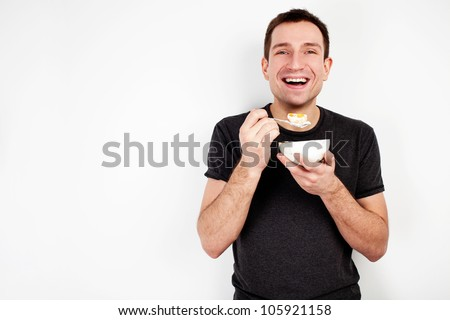 Young smiling man eating cereal on diet isolated on white background - stock photo