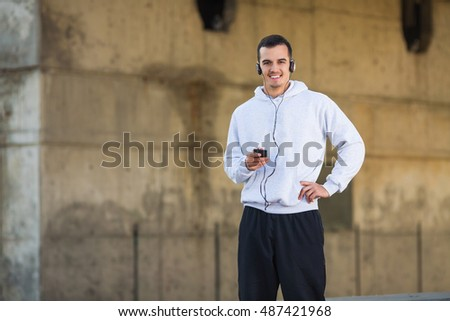 Young smiling man exercising outdoors and listening to a music.