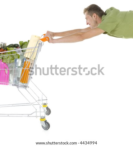Young smiling man holding full of things trolley. Flying with trolley. Side view - stock photo