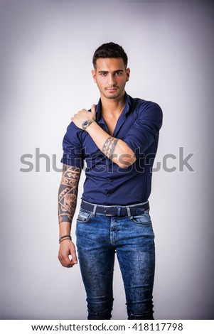 Young smiling man in blue shirt and jeans - stock photo