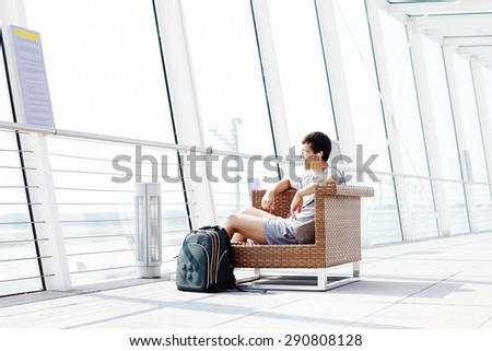 Young smiling man in glasses and headphones sitting on chair in airport departure lounge - stock photo