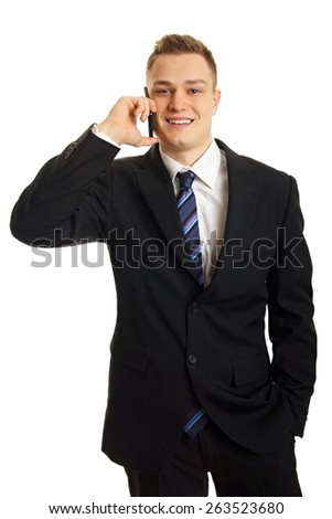 Young smiling man in suit talks into mobile phone - stock photo