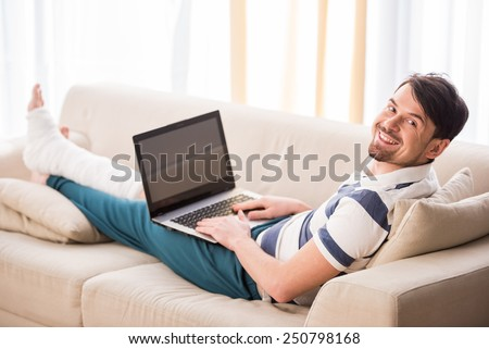 Young smiling man is sitting on sofa with broken leg and using laptop. - stock photo