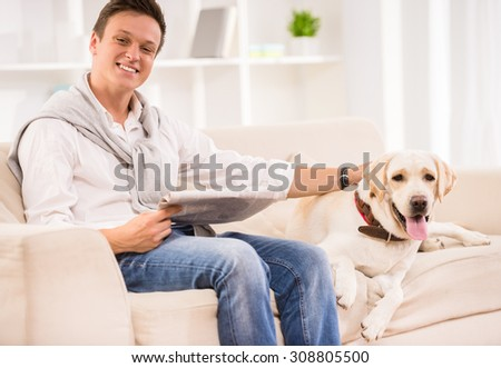 Young smiling man is sitting on sofa with dog and holding a newspaper. - stock photo