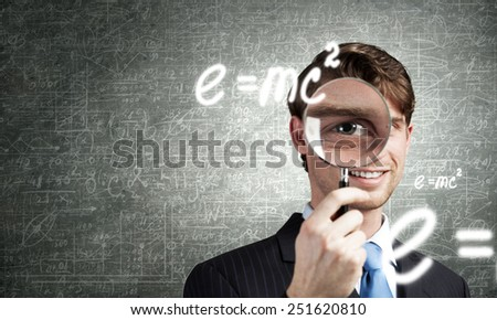 Young smiling man looking in magnifying glass - stock photo