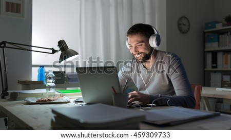 Young smiling man networking and connecting to internet using a laptop late at night, he is sitting at desk and wearing headphones