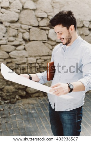 Young smiling man outdoor potrait on a sunny day holding sketching construction project in his hands