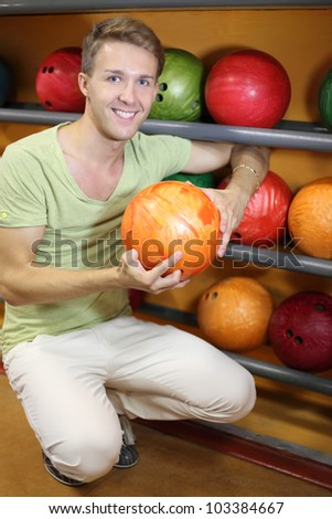 Young smiling man sits near shelves with balls and holds orange ball in bowling club; shallow depth of field