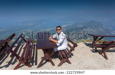 Young smiling man sitting on bench at top of high mountain at sunny day