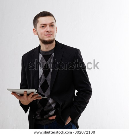 Young smiling man with a beard holding a tablet on a white background. Dressed in a casual