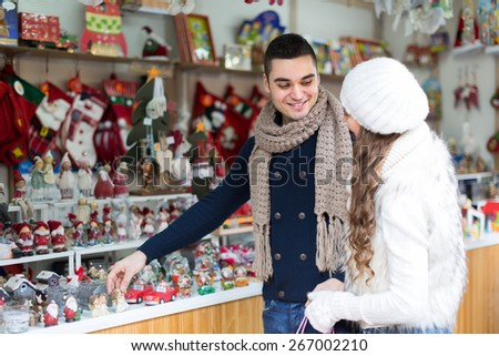 Young smiling man with beautiful girlfriend at counter of X-mas market. Focus  on man