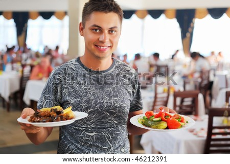 young smiling man with two dishes in hands at restaurant - stock photo