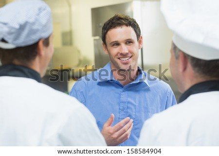 Young smiling manager talking to the staff standing in a kitchen - stock photo