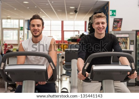 Young smiling men training in the gym with bike.