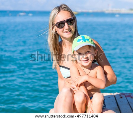 Young smiling mother and baby boy son playing on the beach in the day time