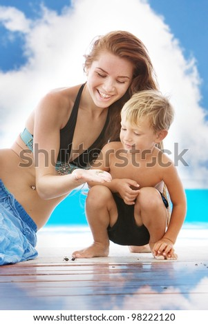 young smiling mother and child near pool on sky background - stock photo