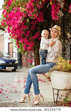 Young smiling mother in a straw hat holding a charming little boy in jeans amid the blooming bougainvillea - stock photo