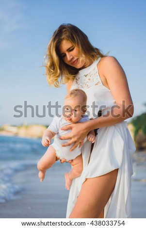 young smiling mother in flying white dress with her baby on the beach . Mother holds newborn baby in her arms . Happy woman with a child smiling and kissing her baby. close up portrait out door