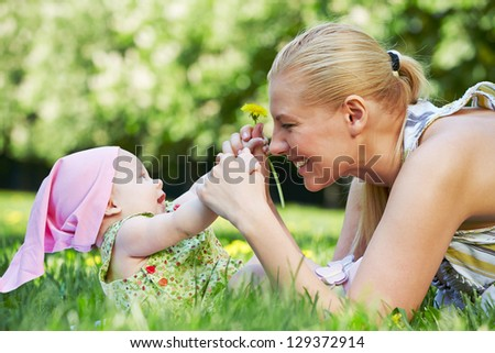 Young smiling mother plays with her baby on grass in spring park - stock photo