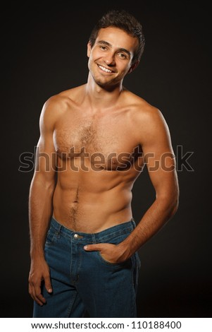 Young smiling muscular male shirtless standing shirtless with hand in pocket over black background - stock photo