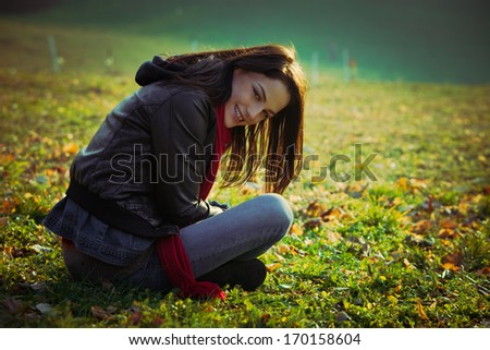 young smiling ordinary  woman sit on grass on field  - stock photo