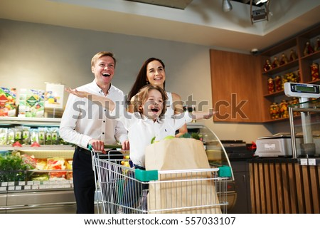 Young smiling parents and their cute kid with shopping cart full of fresh food having fun in grocery department store, boy sitting in shopping cart