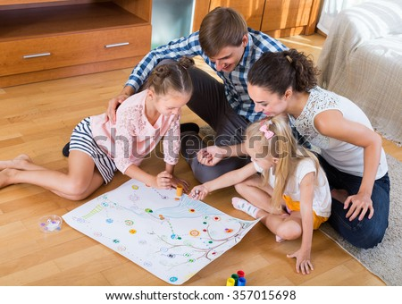 Young smiling parents and two little daughters playing board game at home  - stock photo