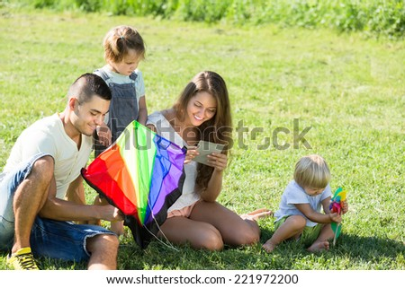 Young smiling parents with children and colorful kite on vacation day  - stock photo