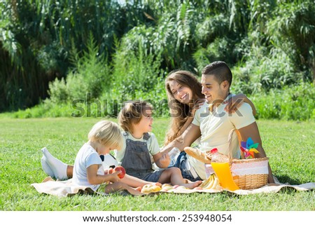 Young smiling parents with little daughters having holiday with picnic at park