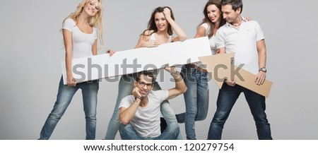 Young smiling people with empty board - stock photo