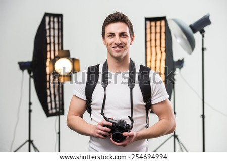 Young smiling photographer with camera in professionally equipped studio. - stock photo