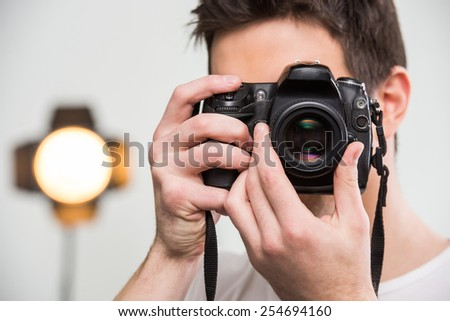 Young smiling photographer with camera in professionally equipped studio. Close-up. - stock photo