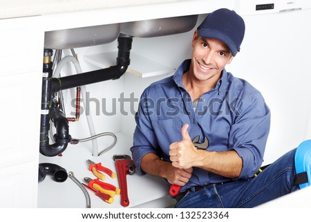Young smiling plumber fixing a sink in the kitchen. - stock photo