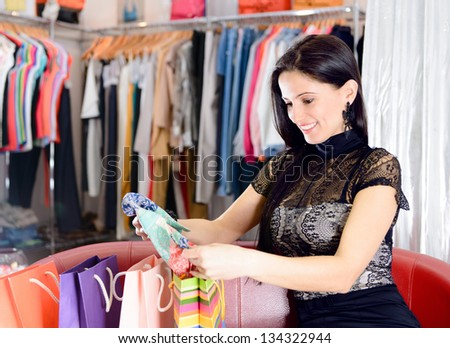 Young smiling pretty brunette shopping in mall - stock photo