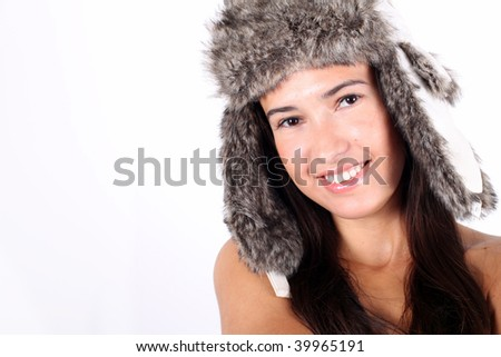 Young smiling pretty girl in a winter hat with ears