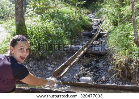 Young smiling pretty woman taking and drinking water from mountain stream with her hands. Enjoying outdoors summer trekking vacation in National park Tscheppaschlucht, Austria