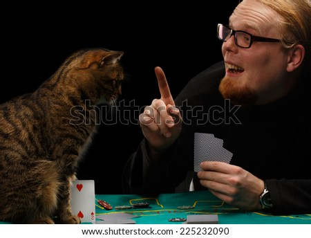 Young smiling red-haired bearded man in glasses holds finger up playing poker with tabby cat sitting at gaming table on black background - stock photo