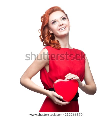 young smiling red-haired caucasian woman in red dress holding red heart isolated on white