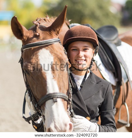 Young smiling rider girl with her horse  - stock photo