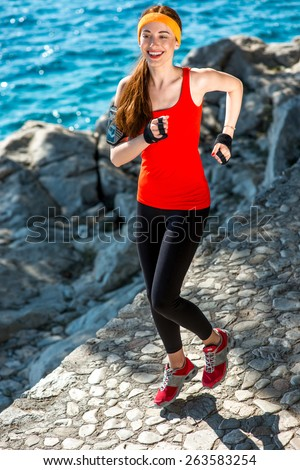 Young smiling sport woman in red shirt running on the rocky path near the sea - stock photo