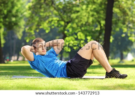 Young smiling sportsman exercising abs in a park