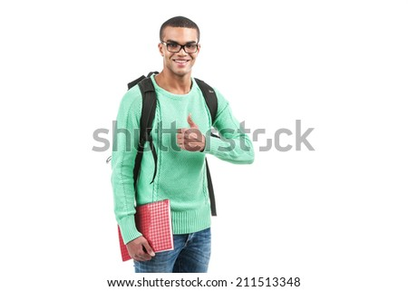 Young smiling student carrying bag. picture of travelling student showing thumb up - stock photo