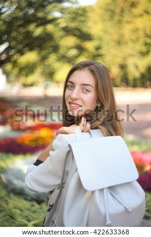 Young smiling student girl with white leather bag in the park. Cheerful happy girl with stylish backpack - stock photo