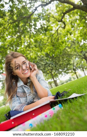 Young smiling student lying on the grass on the phone on college campus - stock photo