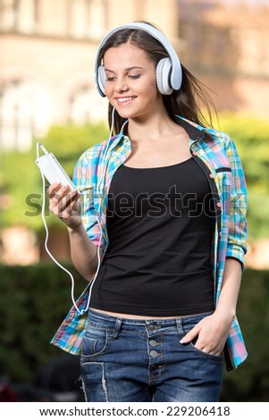 Young smiling student with phone and headphones. The university building in the background. - stock photo